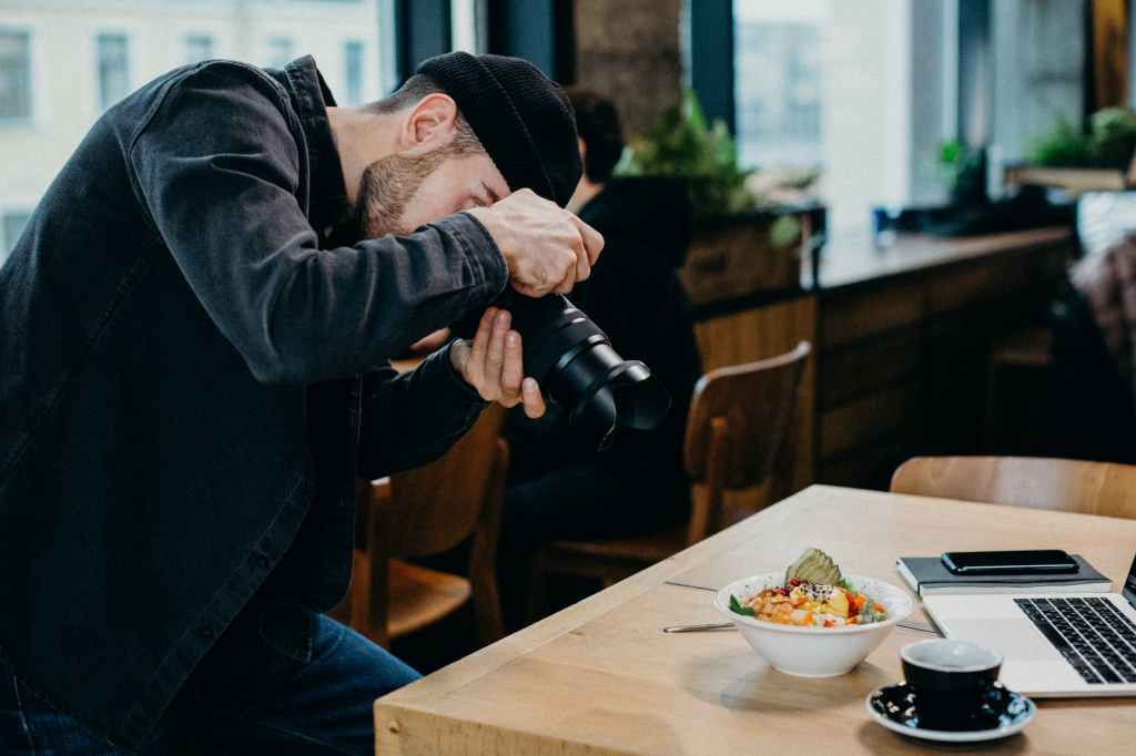 man taking picture of food on top of table inside restaurant